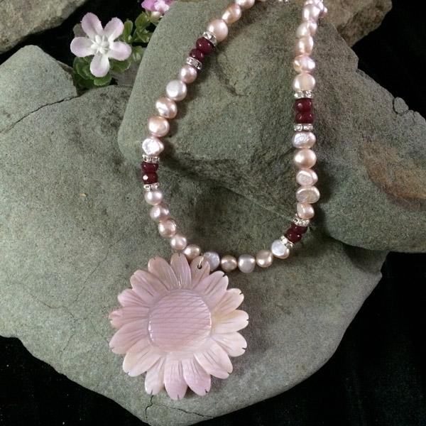 Pink dyed fresh water pearls with silver rondelle and red accent beads and a pink shell flower pendant